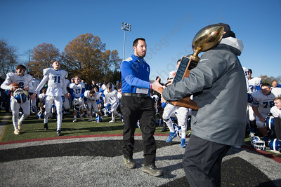 Southington's head coach Mike Drury accespts the Apple Classic Trophy from Athletic Director Greg Ferry Thursday during the 22nd Annual Apple Classic on Thanksgiving Day at Alumni Field on the campus of Cheshire High School in Cheshire. The Blue Knights of Southington defeated the Cheshire Rams 30 to 22. November 23, 2017 | Justin Weekes / For the Record-Journal