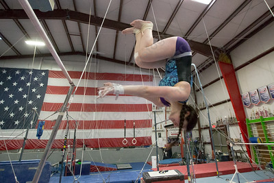 Southington's Katarina Rothstein spots her landing on the dismoint from uneven bars Wednesday during practice at American Gymnastic Training Center in Plantsville  January 10, 2018 | Justin Weekes / Special to the Record-Journal