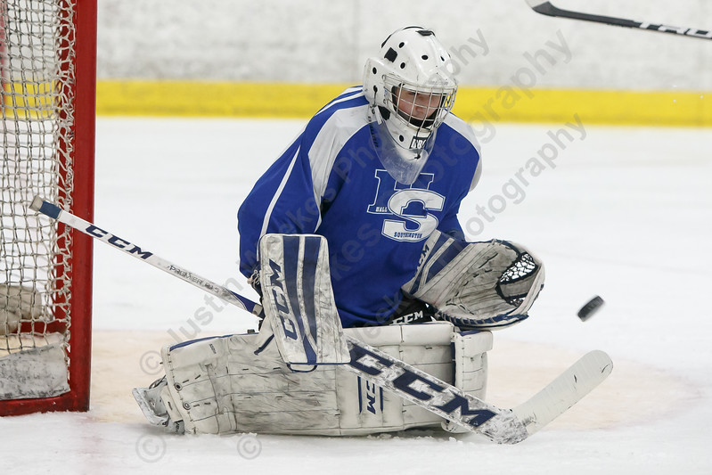 Hall-Southington's Zachary Monti gloves a shot to stop play Saturday during the CCC South Hockey finals at Koeppel Community Sports Center on the campus of Trinity College in Hartford March 3, 2018 | Justin Weekes / Special to the Record-Journal