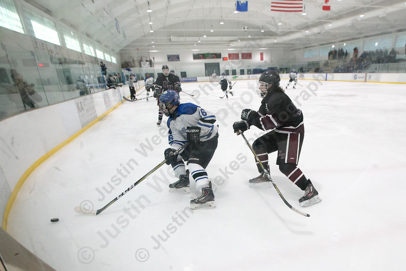 Hall-Southington's Anthony Abbatiello digs a puck out of the corner Saturday at Veterans Memorial Rink in West Hartford January 13, 2018 | Justin Weekes / Special to the Record-Journal