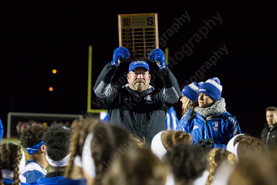 Southington's head coach Charles Kemp raises the plaque celebrating their win Wednesday during the 9th Annual Powder Puff football game at Veterans Memorial Stadium in New Britain. Southington defeated New Britain 20 to 0 to make it two wins in a row. November 22, 2017 | Justin Weekes / For the Record-Journal