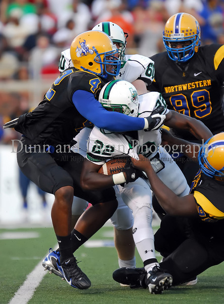 Carroll senior running back Tre' Newton is gang tackled in the game agaisnt Miami Northwestern Saturday night at SMU's Gerald J. Ford Stadium.   Northwestern's defense held Newton to an uncharacteristically low 58 yards for the game.