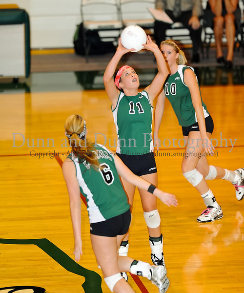 Senior Kristin Duckworth sets the ball as seniors Sally Johnsen and Hannah Herndon prepare for the hit in the match against Plano West Tuesday night at Carroll Senior High School.
