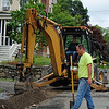 NASHOBA VALLEY VOICE/ANNE O'CONNOR<br /> High Street is getting redone with new drainage and sidewalks. As part of the project, some driveways will be regraded and mailboxes installed on utility poles. Town employee Jimmy  Whitcomb operates the backhoe and Lee Blood is ready to shovel.