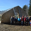 Volunteers gather in front of the High Tunnel for a group picture before pulling the tarp over. SUN/Caley McGuane
