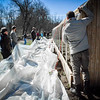 Volunteers set up the tarp that is about to be pulled over the High Tunnel at Littleton Community Farm. SUN/Caley McGuane