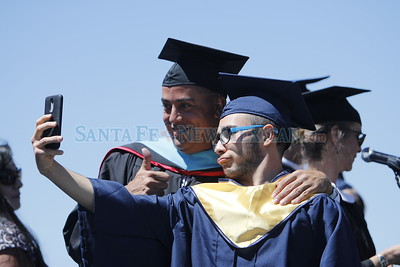 Miguel Diaz, 18, takes a selfie with principal Carl Murano after collecting his diploma at the Santa Fe High School graduation on Friday, May 26, 2017. Luis Sánchez Saturno/The New Mexican