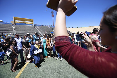 Lizeth Romo, left, takes a picture of her brother Cesar Ismael Romo Perez, 18, surrounded by his family , at the Santa Fe High School graduation on Friday, May 26, 2017. Luis Sánchez Saturno/The New Mexican