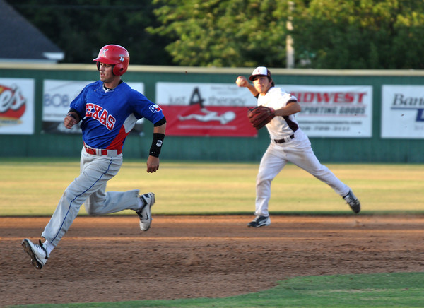 A Texas player runs for third while a Arizona player tries to beat him to the base on Tuesday. Julie Bragg/ The Transcript