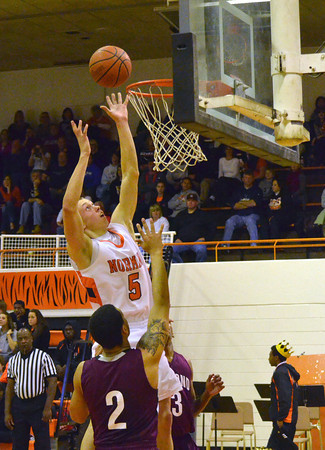 Norman High's George Kittle tips the ball into the basket during the Tigers' game against Edmond Memorial Friday night at Norman high School.<br /> Transcript Photo by Kyle Phillips