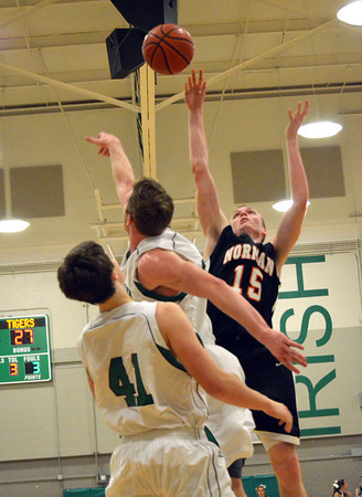 Norman High's Conner Madole gets stuffed by Bishop McGuiness'  Matthew Christiansen as he goes up for a shot during the Tigers' loss to Bishop McGuinness Saturday night at the Bishop McGuiness basketball tournament.<br /> Transcript Photo by Kyle Phillips