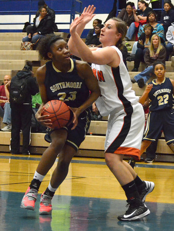 Southmoore's Serinthia Hawkins pushes past Norman High's Taylor Ely during the Sabercat's game against Norman High at the Regional Basketball Tournalment at Choctaw High School.<br /> Kyle Phillips/The Transcript