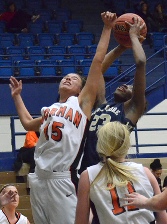 Southmoore's Serithia Hawkins grabs a rebound over Norman High's Lexi Seburg during the Tigers' game against the Sabercats at the Regional Basketball Tournalment at Choctaw High School.<br /> Kyle Phillips/The Transcript