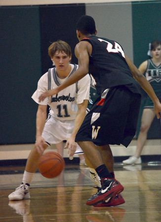 Norman North's Sam Kaplan tries to get around Westmoore's Trey Ayala Tuesday during the Timberwolves' game against the Jaguars.<br /> Transcript Photo by Kyle Phillips