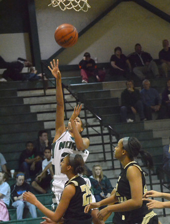 Norman North's Haley Woodard takes a shot from under the goal Tuesday during the Timberwolves' game against Midwest City at Norman North.<br /> Transcript Photo by Kyle Phillips