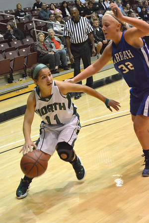 Norman North guard Hayley Scott (11) drives past Harrah's Bailey Mack (32) during the Timberwolves' game against the Harrah High School Friday during the Southern Nazarene basketball tournament.  The Timberwolves <br /> Transcript Photo by Kyle Phillips