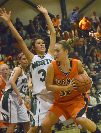 Norman High's Taylor Ely  tries to push past Norman North's Andrea Marris Friday night during the Clash basketball game at Norman North.  The Tigers beat the Timberwolves' on a buzzer-beater shot in the final seconds of the game.<br /> Transcript Photo by Kyle Phillips