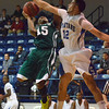 Norman North's Marcus Dickenson (15) gets stuffed by Southeast's Ricardo Deluna (12) Saturday during the Timberwolves' game against the Spartans.<br /> Kyle Phillips/The Transcript