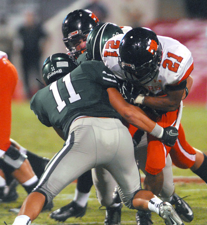 Norman North's DJ Gasso (11) tackles Norman High's Imond Robinson (21) as he runs with the ball  Thursday during the Clash football game at Owen Field.<br /> Kyle Phillips/The Transcript