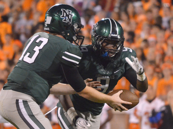 Norman North quarterback Peyton Gravas (13) hands off the ball to Erwin Frazier (9) Thursday during the Clash football game at Owen Field.<br /> Kyle Phillips/The Transcript