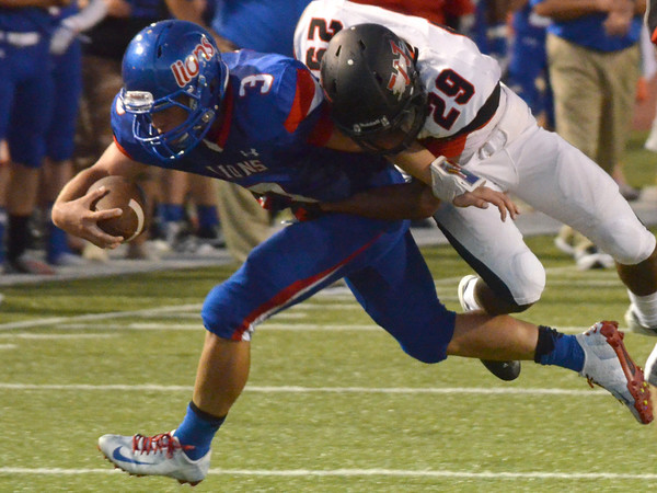 Moore quarterback Derek Harris  (3) is brought down by Westmoore's Giavonni Knight (29) Friday during the Moore War football game.<br /> Kyle Phillips/The Transcript