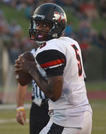 Westmoore quarterback Jhames West (5) looks for an open receiver Friday during the Moore War football game at Moore Stadium.<br /> Kyle Phillips/The Transcript