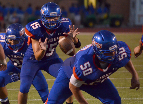 Moore High School quarterback Colin Webb takes a snap Thursday night during the Lions' game against Westmore at the Moore War match in Moore.<br /> Kyle Phillips/The Transcript