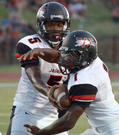 Westmoore quarterback Jhames West (5) hands off the ball to running back Kieron Hardrick (1)  Friday night during the Moore War football game between the Jaugars and Moore High School.<br /> Kyle Phillips/The Transcript