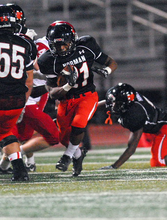 Norman High running back Imond Robinson (21) blasts through the Lawton defense Friday during the Tigers' game against the Wolverines at Harve Collins Field.<br /> Kyle Phillips/The Transcript