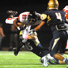 Norman High running back Imond Robinson (21) tries to jump over the Southmoore defense to gain a few extra yards during the Tigers' game against the Sabercats at Moore Stadium.<br /> Kyle Phillips/The Transcript