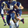 Norman High defender Tywon James pulls down Southmoore running back Pierce Spead (10) Friday night during the Tigers' game against the Sabercats at Moore Stadium.<br /> Kyle Phillips/The Transcript