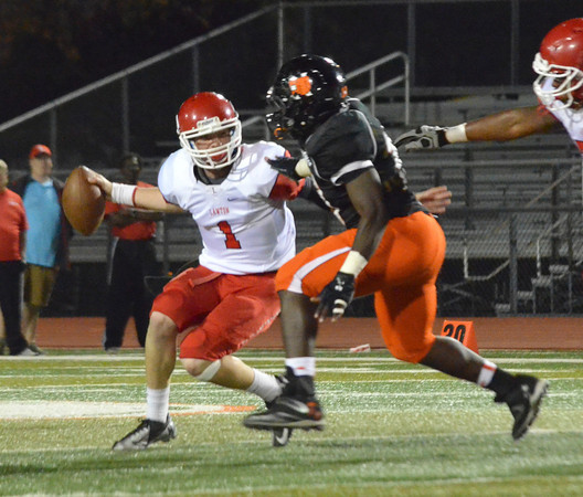 Norman High's Jpsh McGill (10) puts pressure on Lawton quarterback Tevin Foster (1) Friday night during the Tigers' game against the Wolverines at Harve Collins Field.<br /> Kyle Phillips/The Transcript