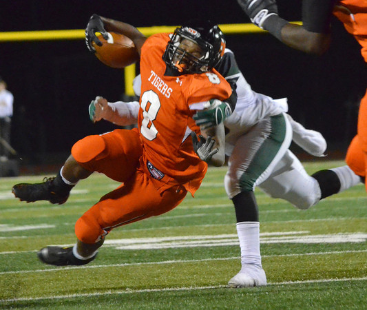 Norman High running back A'enon Hines tries to get past a Edmond Santa Fe defender as he runs with the ball Friday during the Tigers' game against the Wolves at Harve Collins Field.<br /> Kyle Phillips/The Transcript
