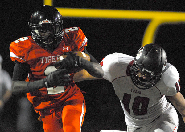 Norman High receiver Jakcob Dean (2) brushes off a tackle by a Yukon defender Friday night during the Tigers' game against the Millers at Harve Collins Field.<br /> Kyle Phillips/The Transcript