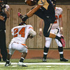 Southmoore's Jackson Stallings (5) hurdles Norman High's Skylar Calhoun (24) as he runs with the ball Friday night during the Tigers' game against the Sabercats at Moore Stadium.<br /> Kyle Phillips/The Transcript