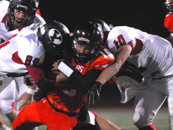 Norman High quarterback Zach Long (16) is hit by two Yukon defenders as he runs the ball Friday night during the Tigers' game against the Millers at Harve Collins Field.<br /> Kyle Phillips/The Transcript