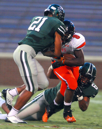 Norman North's DJ Gasso (6) and DJ Hicks (21) bring down Norman High's A'enon Hines (8) Thursday during the Clash football game at Owen Field.<br /> Kyle Phillips/The Transcript