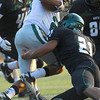 Norman North's DJ Hicks (21) tackles an Edmond Santa Fe player during the Timberwolves' game against Edmond Santa Fe Thursday during a scrimmage at Moore High School.<br /> Kyle Phillips/The Transcript