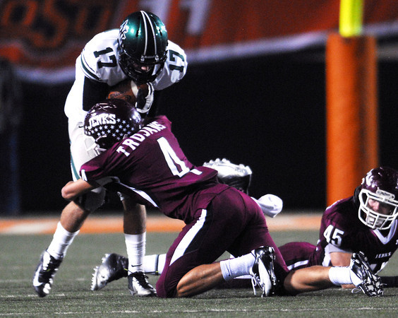 Norman North's Channing Meyer (17) is pulled down by Jenks' Steven Parker (10) Friday during the Timberwolves' game against Jenks in the 6A State championship football game in Stillwater.