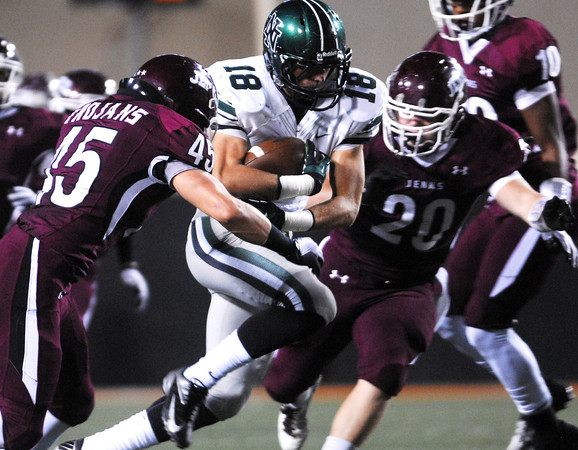 Norman North's Tyler Sipe (18) is pulled down by the Jenks defense Friday during the Timberwolves' game against Jenks in the 6A State championship football game in Stillwater.