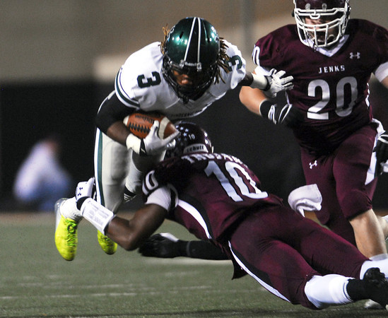 Norman North's Bryan Payne (3) is pulled down by the Jenks' Steven Parker (10)  Friday during the Timberwolves' game against the Trojans in the 6A State championship football game in Stillwater.