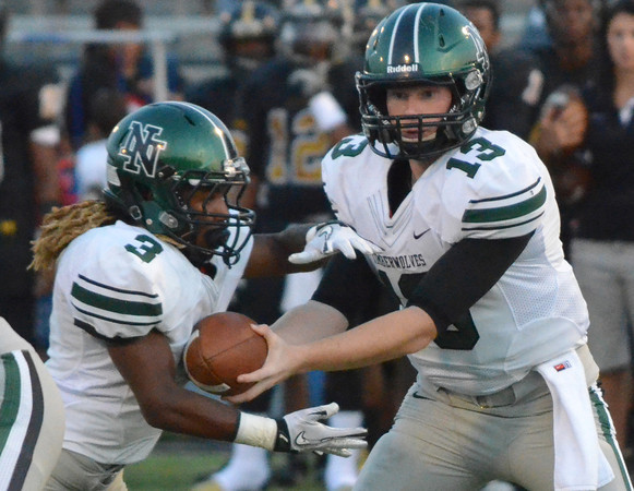 Norman North quarterback Peton Gavras (13) hands off the ball to running back Bryan Payne (3) during the Timberwolves' game against Midwest City.<br /> Kyle Phillips/The Transcript