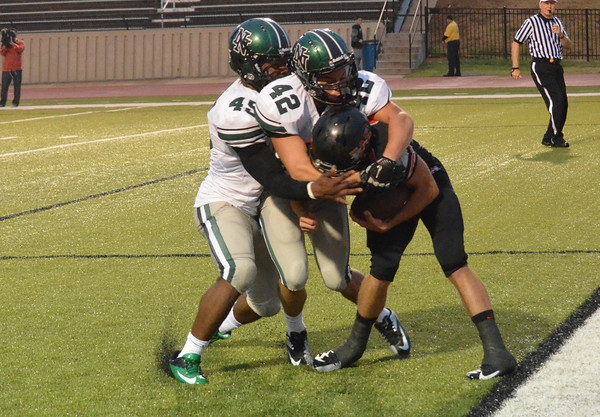 Norman North's Justin Martin (45) and Zeke Burns (42) tackle a Westmoore's Devon Navarro (8) in the end zone for a safety Thursday during the Timberwolves' game against the Jaguars at Moore Stadium.<br /> Kyle Phillips/The Transcript