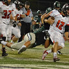 Norman North defender  Evan Coles (68) brings down Yukon quarterback  Hayden Somerville (12) Thursday night during the Timberwolves game against the Millers at Harve Collins Field.<br /> Kyle Phillips/The Transcript
