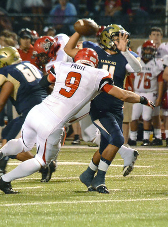 Southmoore quarterback Tre Edwards gets rid of the ball before being hit by a Mustang defender Friday during the Sabercats' game against the Broncos at Moore Stadium.<br /> Kyle Phillips/The Transcript