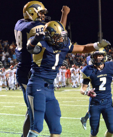Southmoore's Dominique Caster(48) and Nick Ward (1) celebrate after Ward scores a touch down Friday during the Sabercats' game against the Broncos at Moore Stadium.<br /> Kyle Phillips/The Transcript