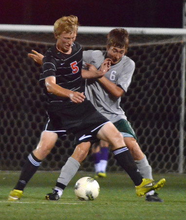 Norman High's Matt Hockett (5) battles Norman North's Michael Hinke (6) for control of the ball Friday night during the Clash soccer match at Norman North.  The Timberwolves won the game 2-1.<br /> Kyle Phillips/The Transcript