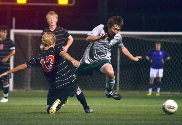 Norman High's J.P. Pelletier (13) trips Norman North's Michael Hinke (6) Friday night during the Clash soccer match at Norman North.  The Timberwolves won the game 2-1.<br /> Kyle Phillips/The Transcript