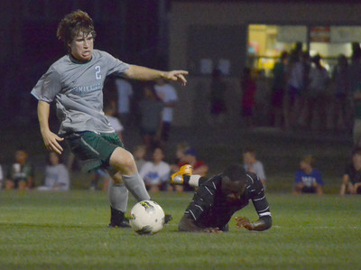 Norman North's Ashton Bray picks up the ball after Norman High's Charles Makinda (10) gets tripped up Friday night during the Clash soccer match at Norman North.  The Timberwolves won the game 2-1. Kyle Phillips/The Transcript