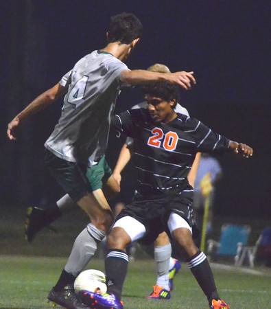 Norman North's Mauro Cichero (14) tries to get the ball away from Norman High's Jorge Briones (20) Friday night during the Clash soccer match at Norman North.  The Timberwolves won the game 2-1.<br /> Kyle Phillips/The Transcript